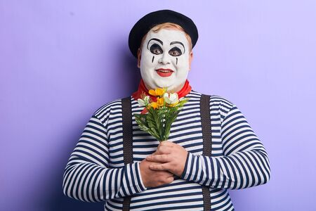 cheerful excited clown preparing a present for woman on birthday, mothers day. celebration, party. entertainment