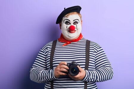 smiling funny clown in stiped sweater holding camera, isolated blue background, studio shot,free time, spare time, leisure