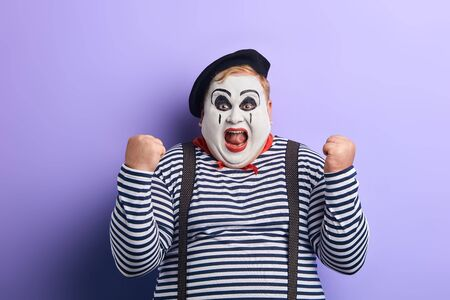 cheerful funny plump mime artist gesturing joy with his hands isolated on blue background. happiness, positive feeling and emotion