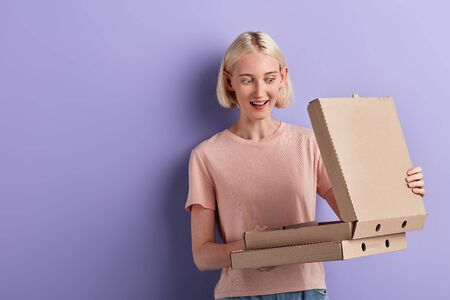 excited surprised girl opening pizza box, treatment, pleasant surprise from boyfriend, breakfast, dinner,close up portrait, copy space Reklamní fotografie