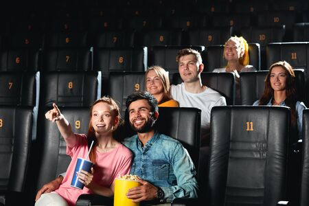 red-haired positive girl pointing to the screen while watching comedy with her boyfriend. look here Stock Photo