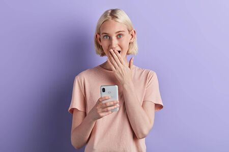 emotional cheeful excited blonde girl holding mobile phone, closing her mouth with palm, girl has received message about winning, close up portrait, isolated violet background