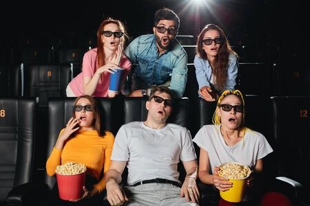 Portrait of an astonished group of young people staring at the screen at the cinema. close up photo. Stock Photo