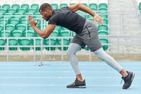 strong motivated active sportsman starting his sprint on running track.strength training. motivation, willpower, full length side view photo