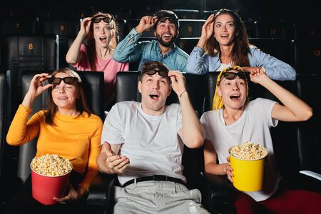young people cheering up and laughing at funny comedy in cinema. Concept of happiness and funny pastime.
