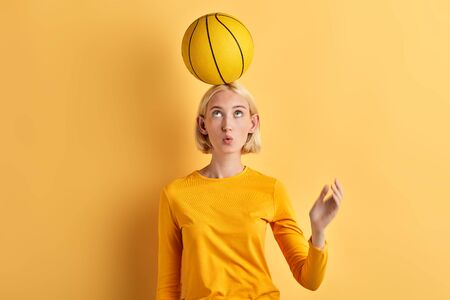 beautiful woman holds basket ball on head isolated on yellow background. close up portrait. studio shot, balance concept. lifestyle, free time. spare time