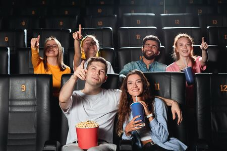 young smiling cheerful friends with popcorn watching film and pointing to the screen in movie theater. close up photo. lifestyle, free time