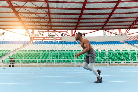 african shirtless spotsman running at the stadium, full length side view photo.motivation, health and body care . copy space . interest and hobby Stockfoto