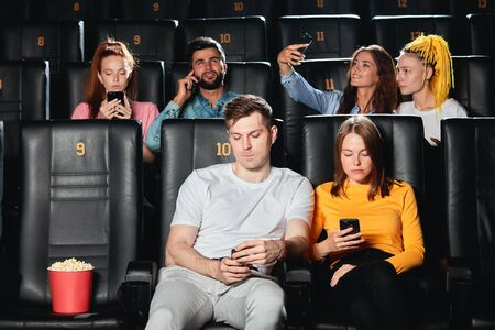 Young caucasian couple feeling bored at cinema session.close up photo. lifestyle, technology. gadget