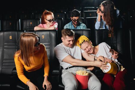 funny man and woman fighting with popcorn during the session at the cinema. close up photo. madness. craziness