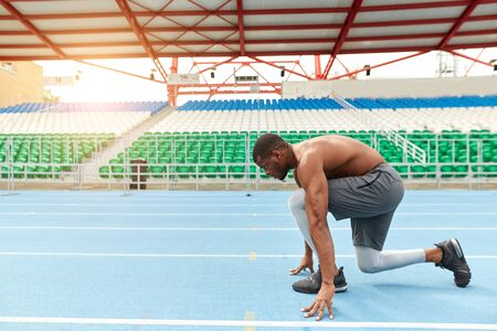 talented african runner is ready to sprint, man standing in the low start position, full length side view photo. copy space Stockfoto