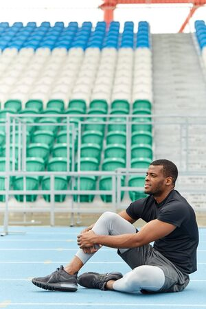 young sportsman thinking about his career, hobby while sitting on the stadium. full length side view photo. lifestyle, colorftoul stadium seats in the background of the pho Reklamní fotografie