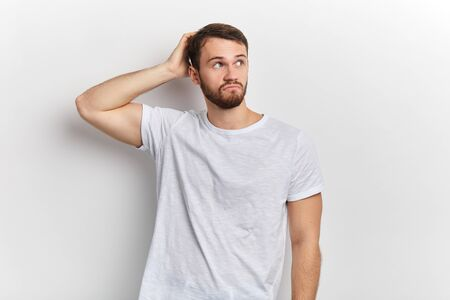 serious man scratching head, thinking deeply about problem trying to solve it, looking up,making decision, isolated on white wall background. Human facial expression, emotion, feeling, body language