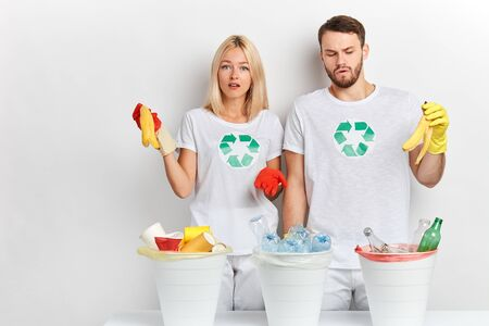 serious woman and handsome man standing near three trash cans, holding banana peel, being puzzled where to throw them family sorting rubbish, throwing banana peel and looking at camera