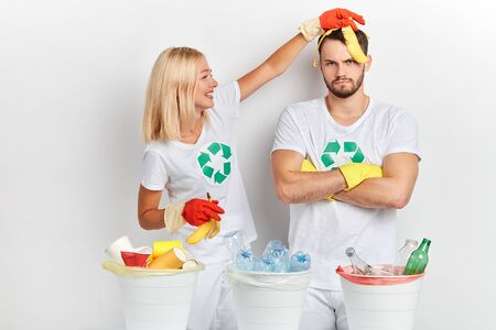 young funny blonde cheerful girl having fun with banana while sorting waste with her frustrated friend , close uop photo. entertainment . Imagens