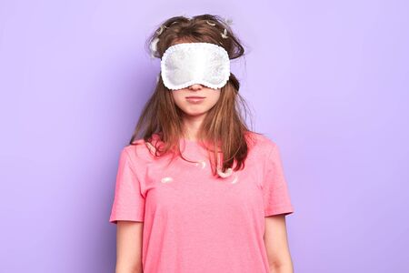 Sleepy student girl with eye mask on doesnt want to wake up, feels tired, studies overtime, prepares for upcoming exam, need lots of strong coffee to feel refreshed, isolated on purple wall.