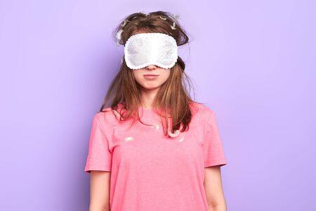 Studentessa assonnata con la maschera per gli occhi non vuole svegliarsi, si sente stanca, studia gli straordinari, si prepara per l'esame imminente, ha bisogno di un sacco di caffè forte per sentirsi rinfrescata, isolata sul muro viola.