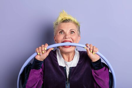 crazy mad old woman with hoop in her mouth, biting hoop with teeth. old woman reducing stress. close up portrait. angry woman is fighting with her old age