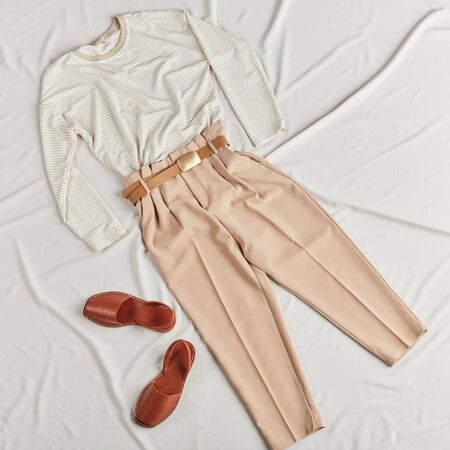 Modern female clothes lying on bed. fashionable clothes on cheap prizes. top view photo. successful shopping concept