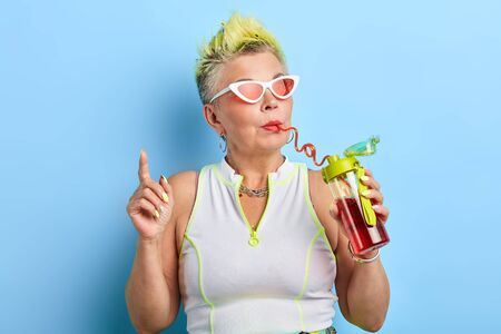 funny woman in sunglasses sipping juice and pointing with index finger up, close up portrait, isolated blue background, studio shot