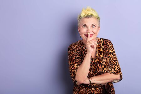 old glamour woman with dyed yellow hairstyle asks to keep secret, isolated over blue background. closeup portrait, copy space. studio shot.lifestyle