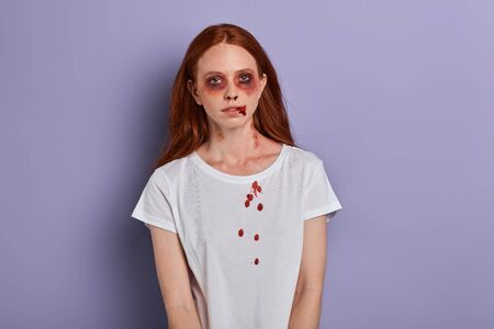red haired sad girl in white T-shirt being hurt by her cruel boyfriend. close up portrait. domestic violence victim.lifestyle concept
