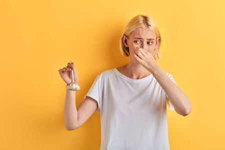 beautiful young woman in white t-shirt closing her nose with fingers, isolated yellow background, studio shot, girl hates garlic, awful smell from it