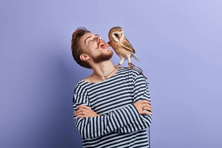 funny crazy man with crossed arms putting tongue out, looking at the owl, close up portrait, isolated blue background .guy teasing his bird
