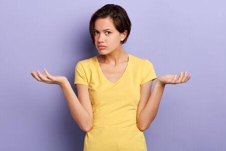 Chica seria no puede entender a su amiga, mujer desconcertada con sugerencia, oferta, retrato de cerca, fondo violeta aislado, foto de estudio