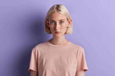jolie jeune femme avec de grandes oreilles en regardant la caméra. portrait en gros plan, fond bleu isolé, tourné en studio