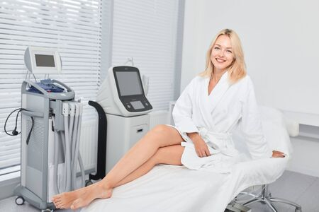 positive fair-haired woman sitting with crossed legs, full length photo.leisure, skin care concept, wellness, wellbeing