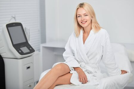 cheerful positive woman in white bathrobe enjoying her day off, businesswoman has a rest indoors