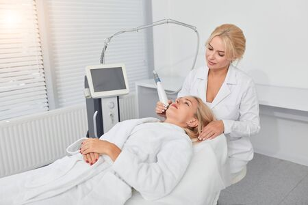 relaxed blonde client treating her unhealthy face at modern clinic. close up photo