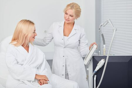 doctor and client talking about modern medicine, doctor consulting woman in bathrobe, showing the screen of tool