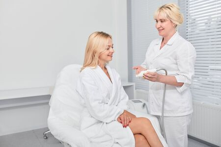 two cheerful women having a conversation at beauty clinic. close up photo. consultation.