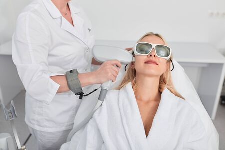 blonde girl gets pleasure from painless process of removing the hair from the skin surface, close up photo. relaxation Stockfoto