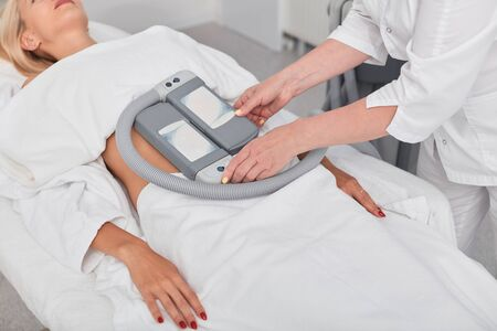 talented cosmetologist preparing patient for cryolipolysis process. close up cropped photo. new modern technology, beauty care Stockfoto