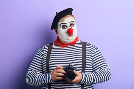 funny serious mime taking photo with film camera isolated on blue. hobby, interest, lifestyle.