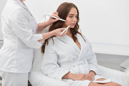 awesome good looking girl in white bathrobe receiving stimulating electric facial treatment from therapist, close up photo, wellness, wellbeing