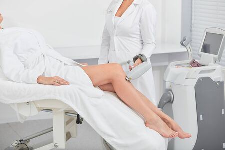 nurse using a laser hair removal at workplace, close up cropped photo, new removal techniques Stockfoto