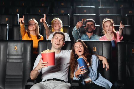 positive couple enjoying watching the romantic comedy, while people who are sitting behind them are pointing at the screen. leisure time, pastime Banco de Imagens