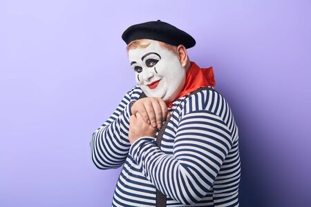 friendly kind clown in striped sweater, red kerchief around neck and black hat expresses tender feeling, sweetheart.