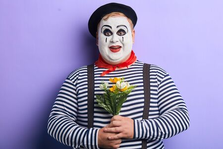 positive funny mime with a bunch of wonderful flowers posing to the camera, isolated blue background, happiness, surprise Stock Photo