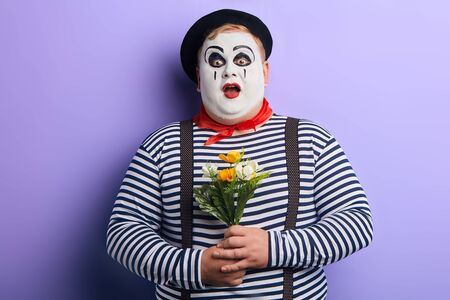 surprised shocked young man with painted face, striped clothes and suspenders with wide open mouth holding bouquet of artificial flowers.isolated blue background, studio shot