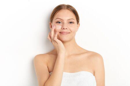 smiling girl massaging her face , taking care of skin. close up portrait, wellness, wellbeing . close up portrait Reklamní fotografie