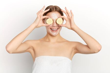 smiling girl with facial mask and cucumber slices in her hands having fun, close up portrait, isolated white background, studio shot, beauty, wellness and wellbeing