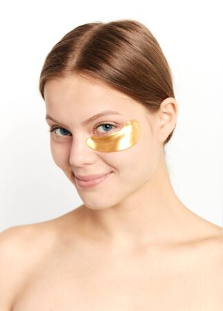 effective gold patch for dry skin, acne, wrinkles, close up portrait, isolated white background, studio shot.