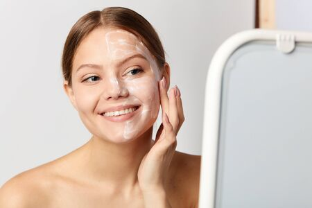 young positive girl applying cream on face. skin and health care. healthy lifestyle. close up portrait