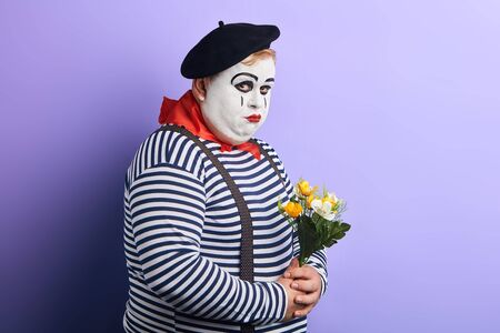 Sad depressed mime artist holding a bouquet of flowers isolated on blue background. depression, loneliness, negative feeling and emotion. copy space