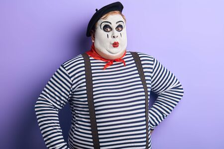 awesome man with painted face amusing audience. close up photo. isolated blue backround, studio shot. Stock Photo